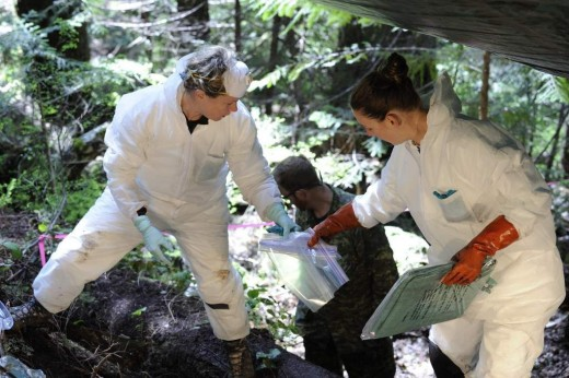 On May 5, 2014, Courtney Brown, coroner, British Columbia Coroners Service, right, and Laurel Clegg, a forensic scientist and casualty identification coordinator with the Directorate of History and Heritage in Ottawa, conduct an initial survey and recovery of the remains of four airmen from the crash of a Second World War training aircraft in British Columbia.