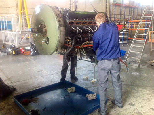 Technicians pull accessories off a damaged Merlin engine to install on a replacement Merlin for the CWH Lancaster